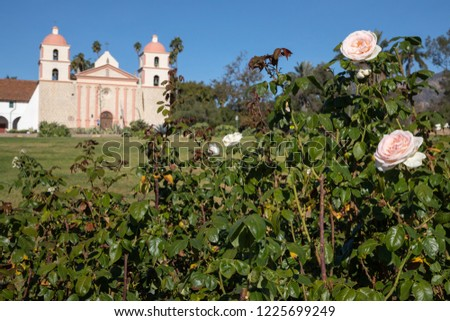 Pink rose with the Spanish style Santa Barbara Mission chapel in the background, and space for text on the bottom #1225699249