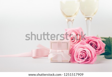 Pink roses, a gift with a silk ribbon and glasses on a light pastel background. Delicate bouquet and a gift for a solemn event. Selective focus. Copy space.