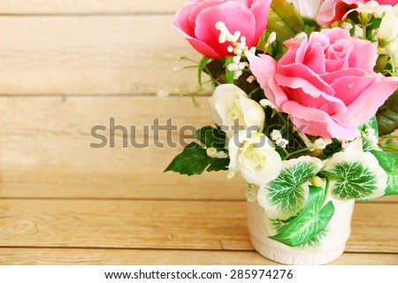 Pink roses against a wood wall