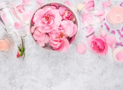 Pink roses cosmetics set with cream,bottle,candles, petals and sea salt, spa background with space for text, top view