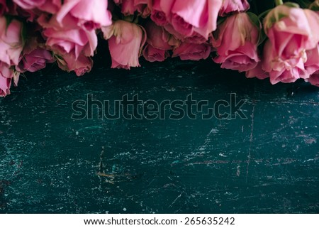 Pink roses frame, on a wooden, vintage blue tabe; with place for text