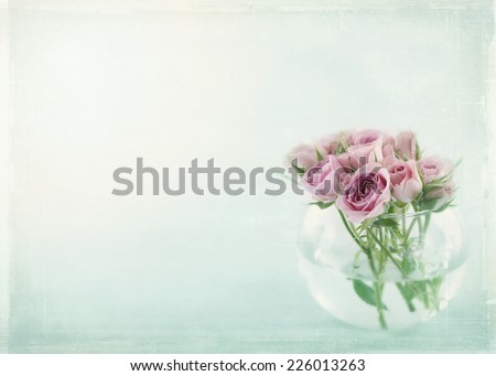 Pink roses in a glass vase filled with water on light blue background with vintage textured editing