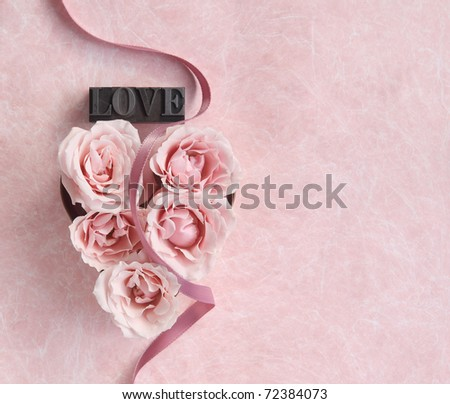 pink roses in a heart shape with a ribbon and copy space