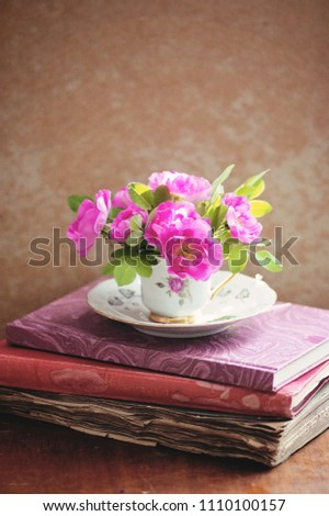 Pink roses in a teacup on a stack of old books #1110100157