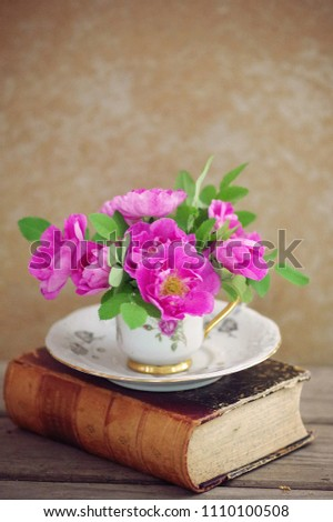 Pink roses in a teacup on top of an old book #1110100508