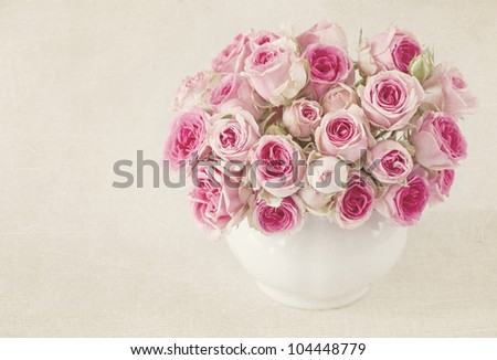 Pink roses in a vase on grey background