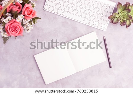 Pink roses on grey table with white keyboard and open notebook. Artist workplace, office concepr. Text space #760253815