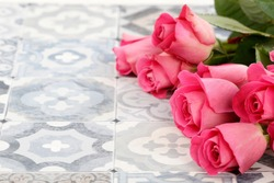 Pink roses on traditional portuguese floor tiles.