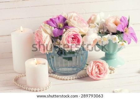 Pink roses, white jasmine and violet clematis flowers and candles on white  wooden background.  Selective focus.  Toned image.