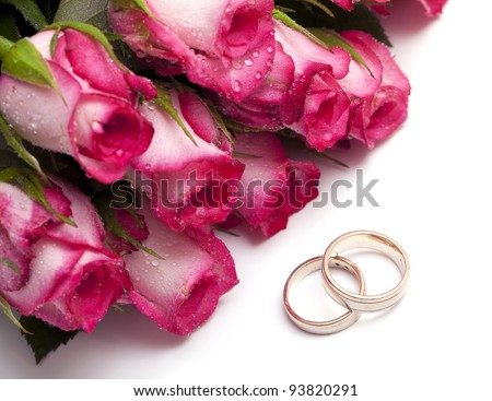 pink roses with droplets and wedding rings isolated on white