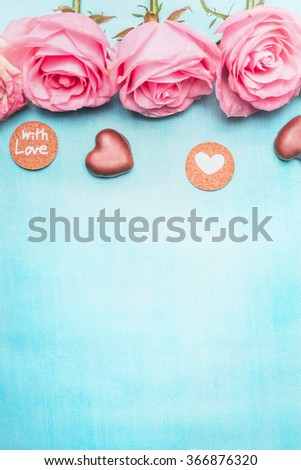 Pink roses with heart chocolate and romantic love message on blue background, top view. Valentine\'s Day or Birthday greeting card