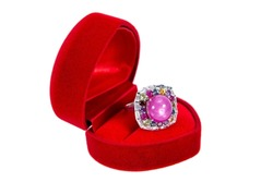 Pink ruby ring in ring box isolated on white background. large pink ruby gem ring surrounded with colorful gems in red velvet ring box heart shape isolated