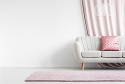 Pink rug in front of white sofa with satin pillow in bright living room interior with empty wall