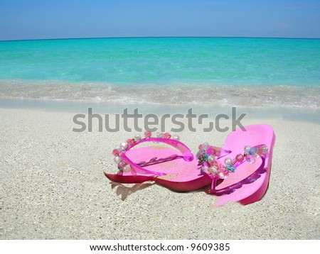 pink sandals on the shoreline of a tropical beach