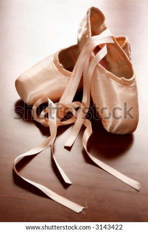 Pink satin ballet shoes on dark floor in slight soft focus