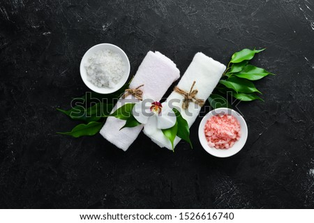 Pink sea salt with towels and tropical leaf. On a black stone background. Spa treatments. Top view. Free space for your text. #1526616740