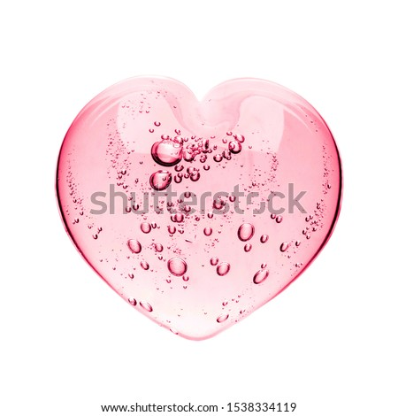 Pink serum gel, heart shape puddle isolated on white backdrop, top view. Squeezed transparent care gel with bubbles close up, macro isolated on white background.