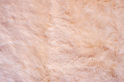 Pink shaggy blanket texture as background. Fluffy fake textile fur.