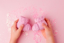 Pink shoes for newly born baby girl in kids hands on pink background, concept of expectation of baby, pregnancy, baby shower party, cute monochrome card for congratulation, banner