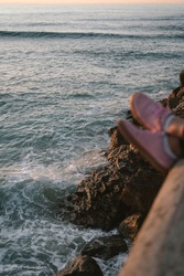 Pink shoes hanging off a ledge above the sea