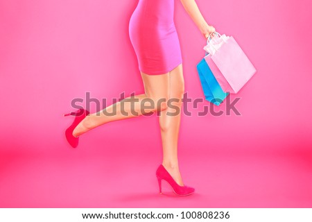 Pink shopping. Woman shopper legs, high heels and shopping bags on pink background.