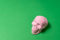 Pink skull on green background. Minimal Halloween concept.