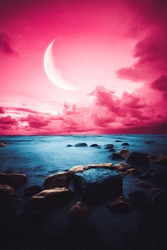 Pink sky over sea with big moon and golden rocks