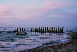pink sky sunset old bridge beams breakwater sea
