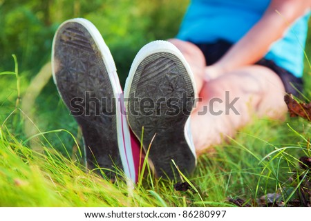 Pink sneakers on girl legs on grass during sunny summer day.