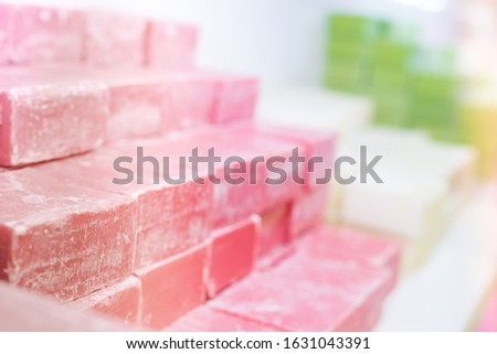 Pink soap pieces in the store with many other colorful turkish soaps on display for customers. Blank space background