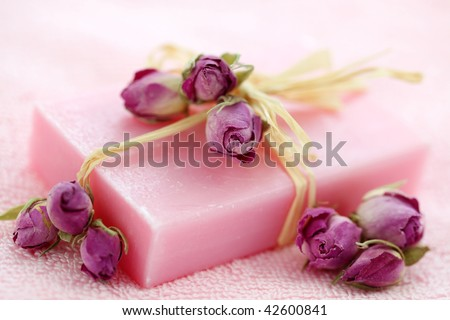 Pink soap with dried roses on towel