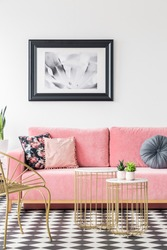 Pink sofa decorated with pillows, poster on the wall and golden tables in a living room interior. Real photo