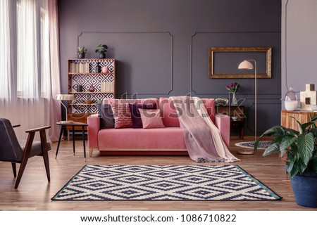 Pink sofa with two blankets and cushions standing in sitting room interior with windows with curtains, patterned carpet and empty frame on the wall