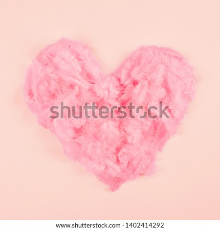 Pink soft feather heart shape on peach colored background #1402414292