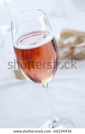 Pink sparkling wine on a white cloth in champagne flute with a ribbon in the background.