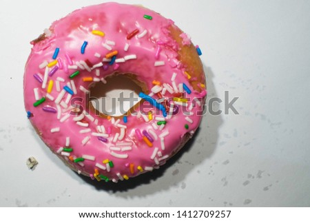 Pink sprinkled doughnut isolated on a white background