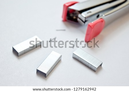 Pink stapler and staples on white background - selective focus -image