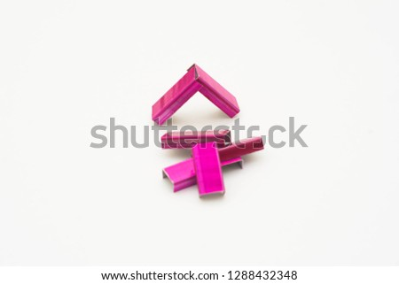 Pink stapler pin on white background.