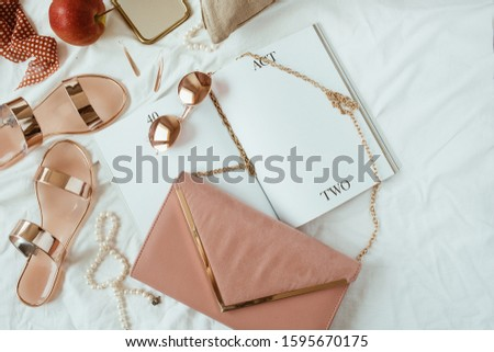 Pink styled women fashion composition with female accessories, bijouterie, accessories on white linen in bed. Flat lay, top view template for social media, website, magazine.