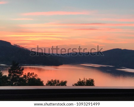 Pink summer sunset over calm waters of Brno reservoir, Czech Republic. Silhouettes of hills and mountains on the background. Sky reflection on water surface. Barrier in front. Cloudy sky. Dusk. #1093291499