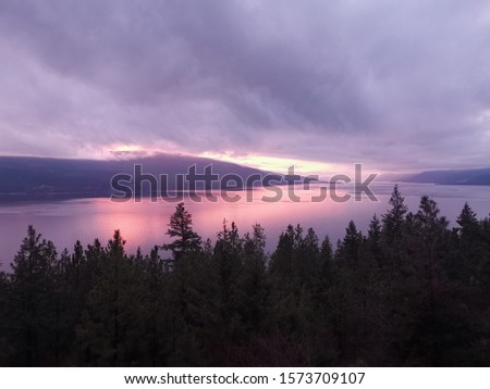 pink sunrise over the lake with views of the spruce trees and mountain ranges.  #1573709107