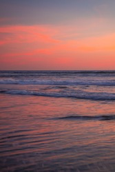 Pink sunset on the beach. Seascape for background. Colorful sky. Beautiful water reflection. Sunlight on horizon line. Nature and environment concept. Copy space. Sunset in Bali, Indonesia.