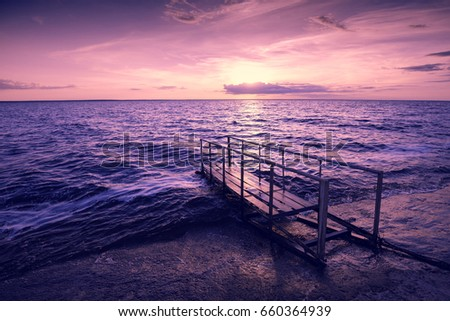 Pink sunset over sea, pier on the sea #660364939