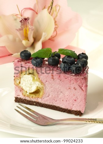 Pink sweet birthday cake with orchid in a background