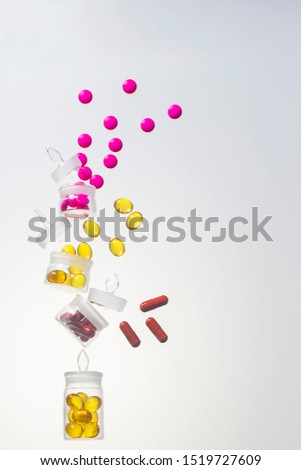 pink tablets, burgundy capsules and transparent capsules of omega fatty acids in chemical dishes crumbled
