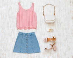 Pink tank top, blue denim mini skirt, small white cross body bag with chain strap, pink block heeled sandals on white wooden background. Woman's casual day outfit. Trendy spring summer look. Flat lay.