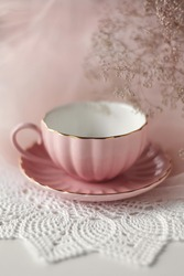 Pink tea cup in a saucer with gold trim on a white table with a crochet white doily dried flowers and pink tulle in the background