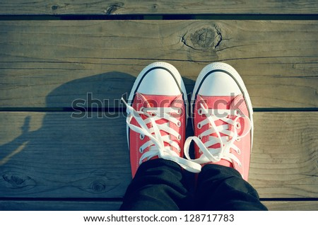 Pink tennis shoes on a beach boardwalk - stock photo