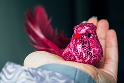 Pink textile bird with a body covered with a net and sparkles, a tail made of real feathers, black eyes and an orange beak in the palm of a female hand. Selective focus