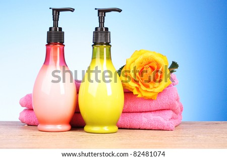 Pink  towels, soap bar and yellow rose on blue